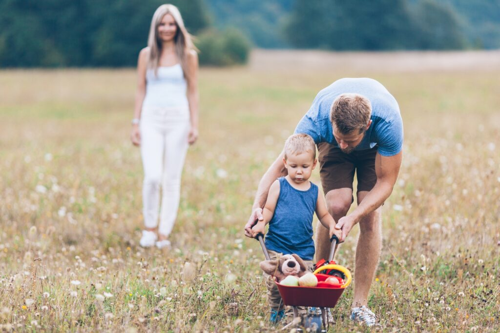 Child with his parents pushing a whellbarrow outdoors