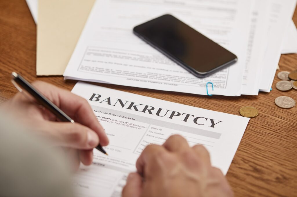 partial view of businessman filling in bankruptcy form at wooden table with smartphone